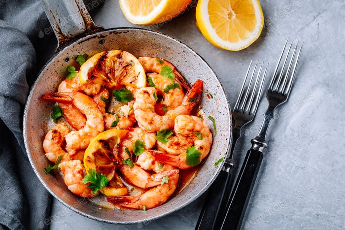 Spicy garlic chilli Shrimps on frying pan with lemon and cilantro