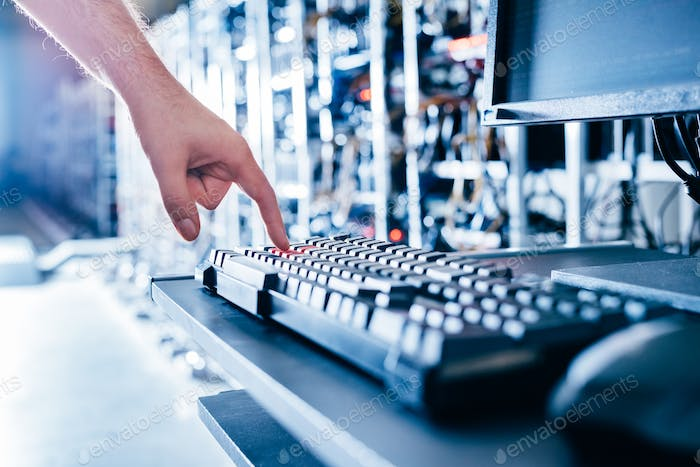 IT specialist pressing red button on keyboard in big data center.