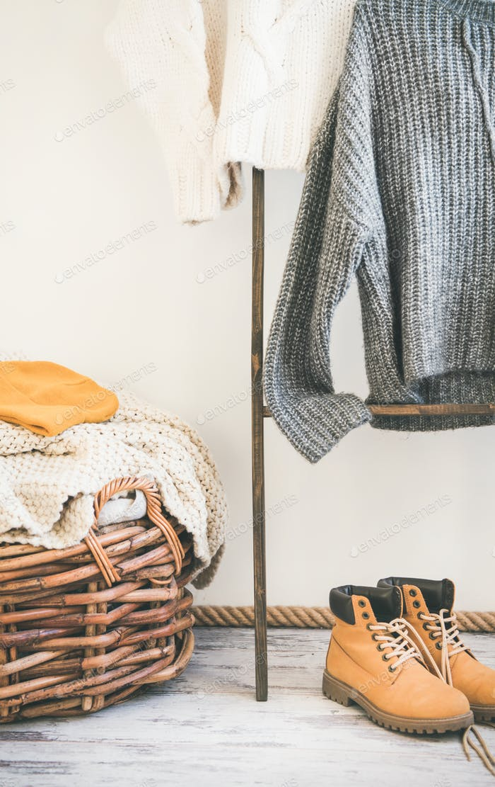 Fall or winter warm knitwear on hanger, white wall background