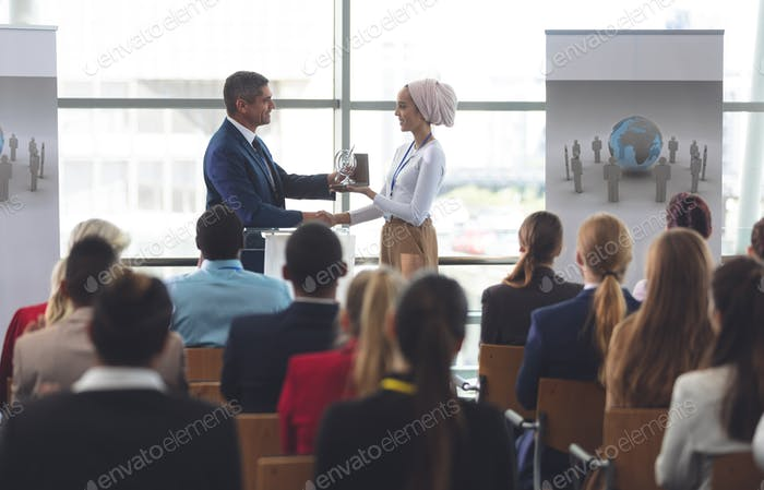 Businesswoman receiving award from black businessman at business seminar in office building