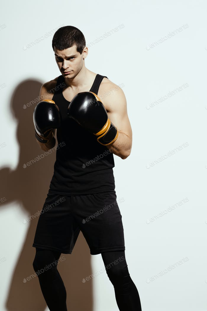 Ready to fight tall attractive sportsman posing in boxing gloves over white background