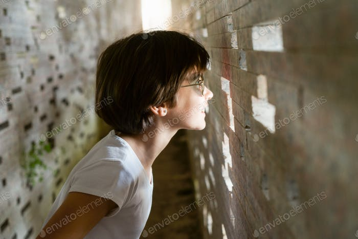 Child looking through the bricks inside the Nazari Wall