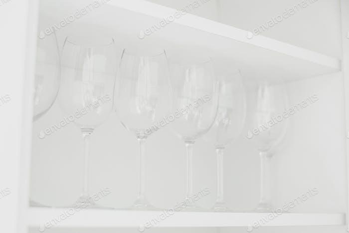 Transparent glasses on white shelf