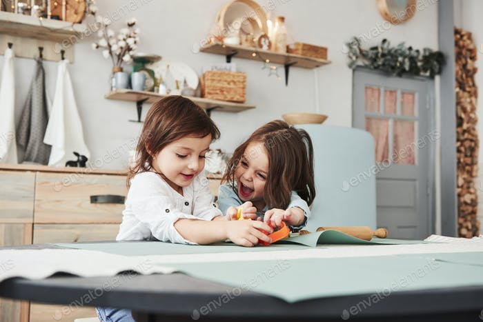 Happy childhood. Two kids playing with yellow and orange toys in the white kitchen
