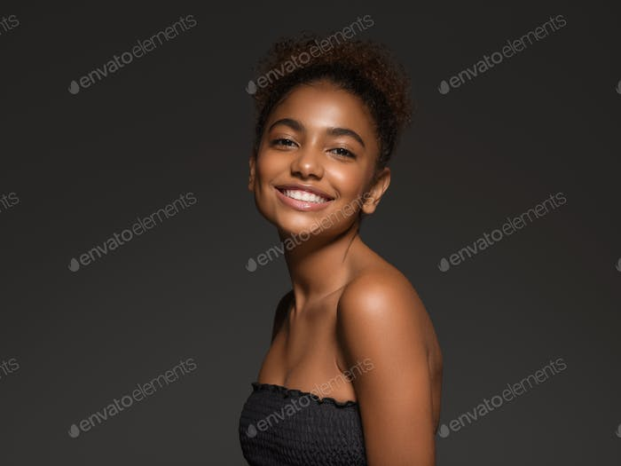 Beauty woman black skin face smiling model face in black top. Black background.
