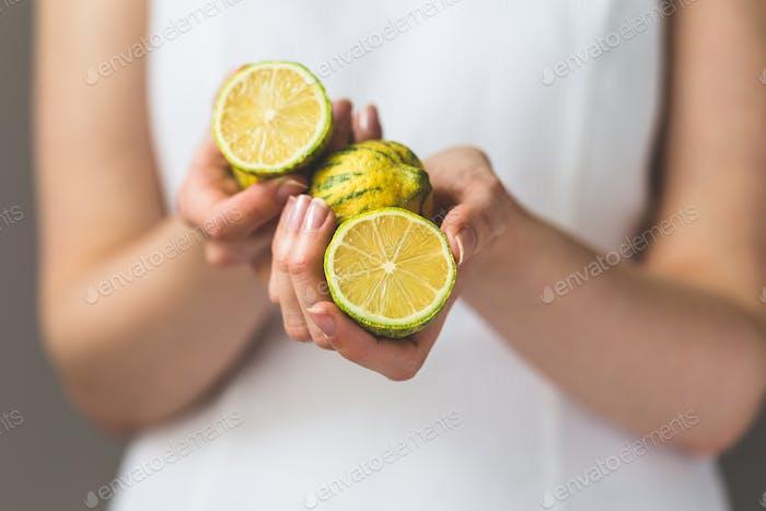 Weiblich halten Zitronen in Händen