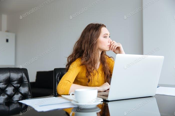 Продуманная женщина сидит за столом