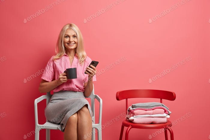 Glad fifty years old woman sits on chair drinks tea or coffee and uses mobile phone for surfing soci
