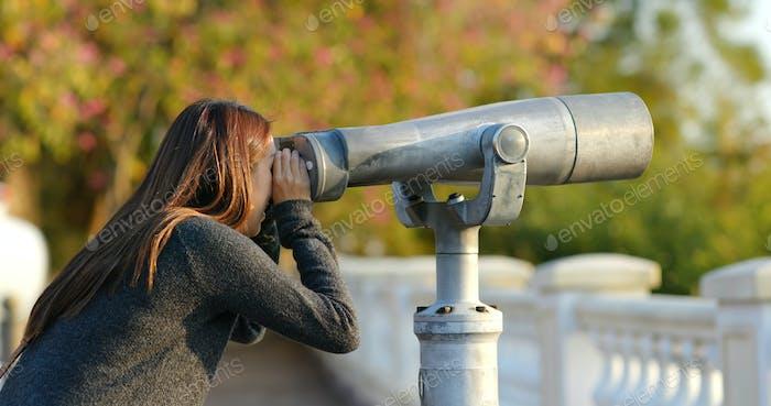Mujer turista mirando a través del binocular al aire libre