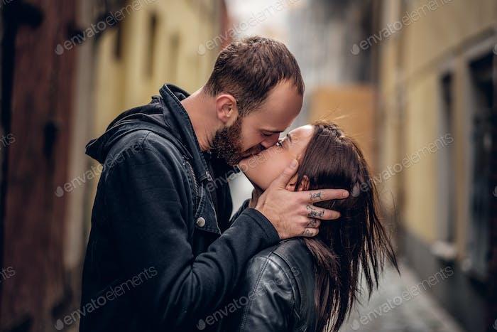 Positive bearded male kissing cute brunette female.