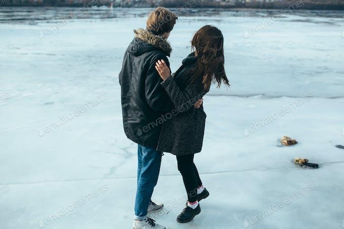 junges schönes Paar auf dem Eis eines gefrorenen Sees
