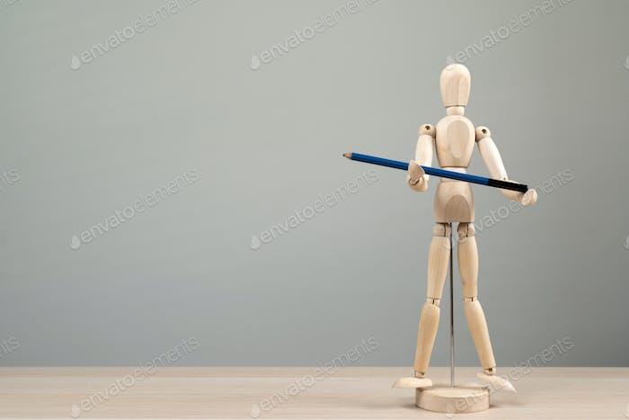 Wooden figure mannequin holding blue pencil