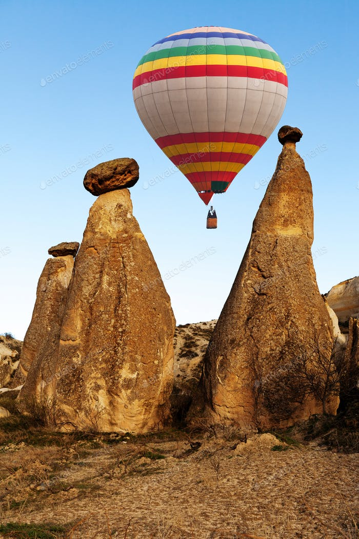 Hot air baloon flying over spectacular stone cliffs in Cappadocia