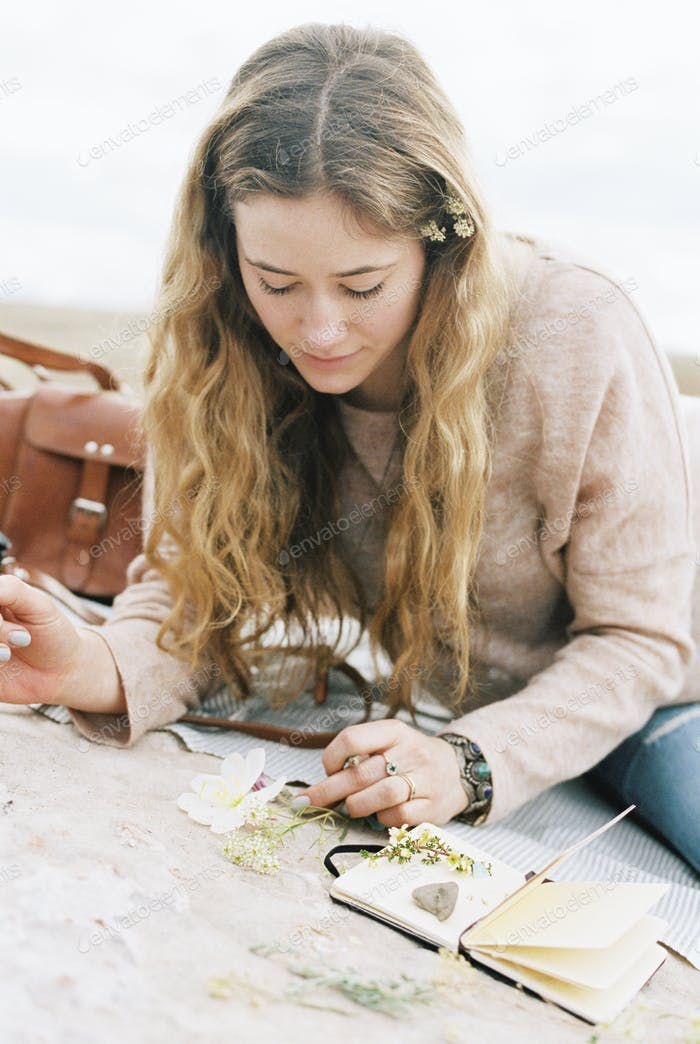 Woman sitting on a rock, putting wild flowers between the pages of a notebook.