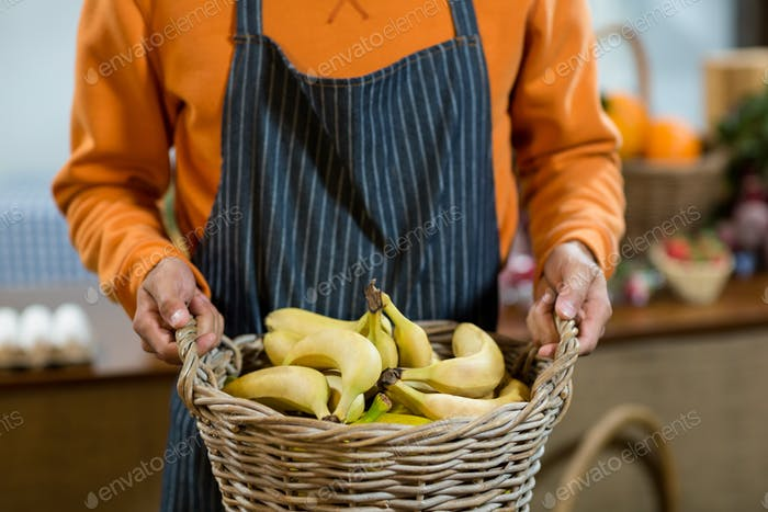 Vendor holding a basket of bananas