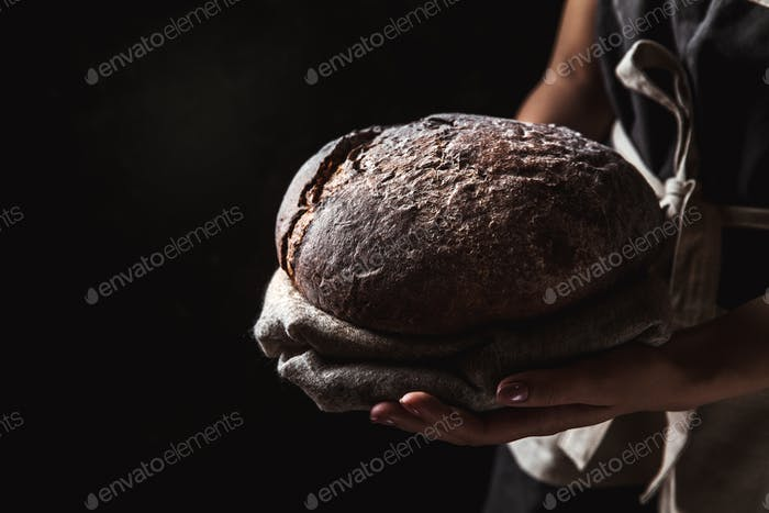 rustic bread in baker hand, healthy food