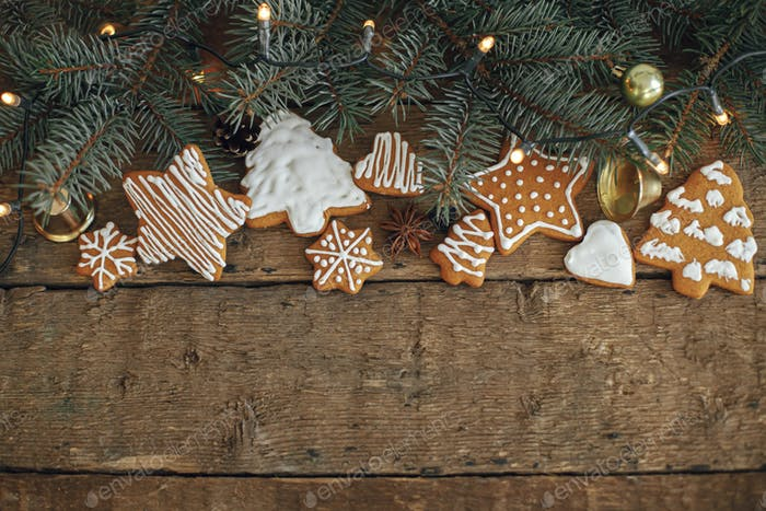 Christmas rustic flat lay. Christmas gingerbread cookies, fir branches, warm lights on rustic wood