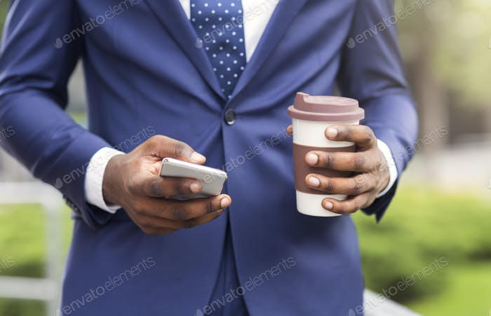 Busy businessman using smartphone and drinking take-out coffee outdoors