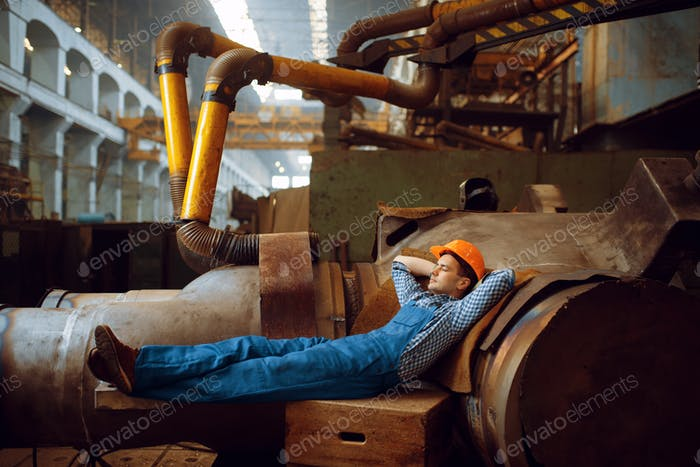 Male worker resting at lunchtime on factory