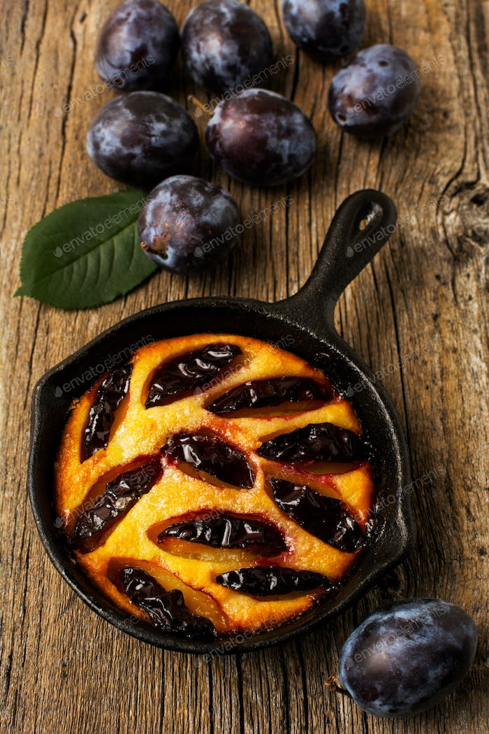 Cast iron plum pie on the rustic table