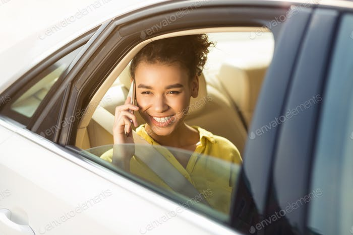 Happy woman sitting in car and talking on phone