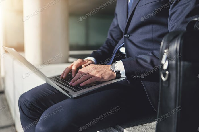 Sitting businessman working with a gray laptop