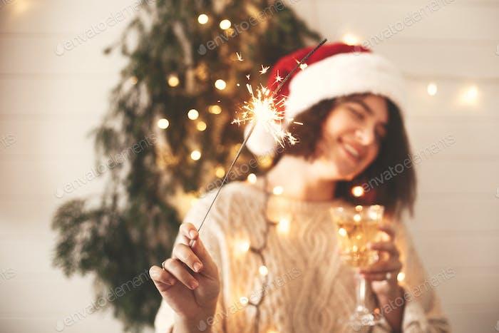 Sparkler burning in hand of stylish happy girl in santa hat