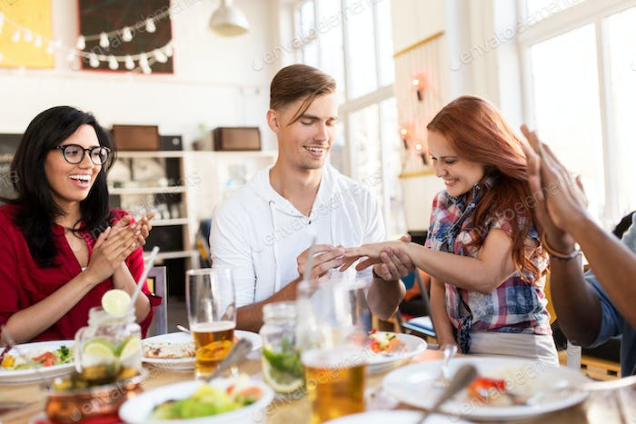 happy man doing proposal to woman at restaurant