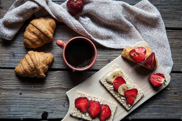delicious breakfast with a cup of coffee and fruit sandwiches, croissants. Strawberries, food, drink