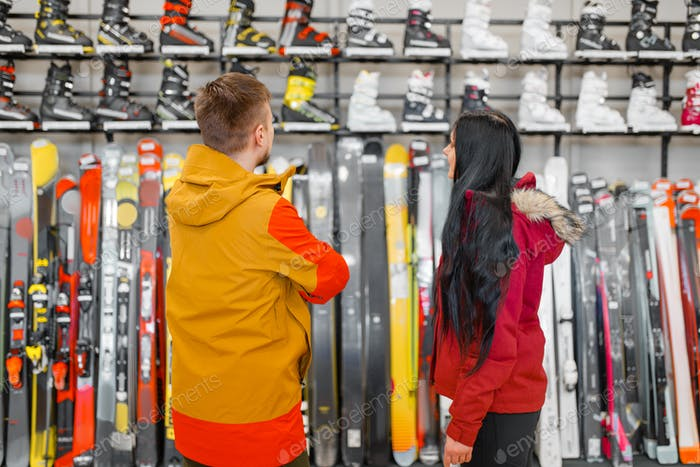 Couple choosing skiing or snowboarding equipment