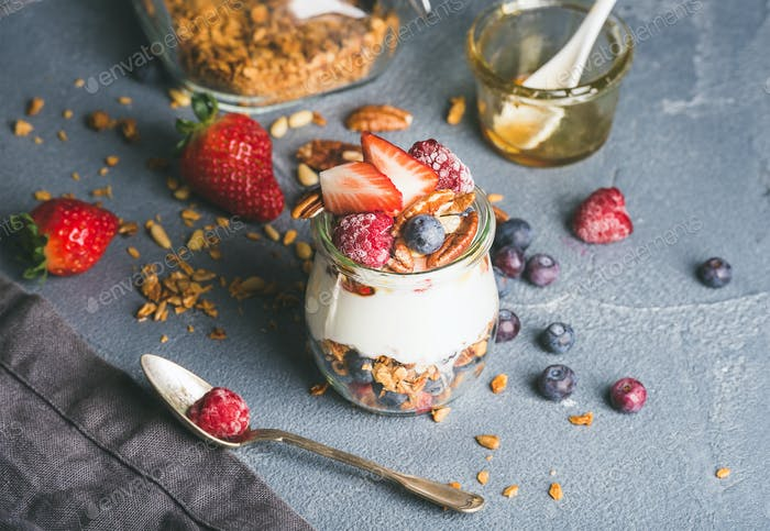 Yogurt oat granola with fresh berries, nuts, honey and mint leaves in glass jar