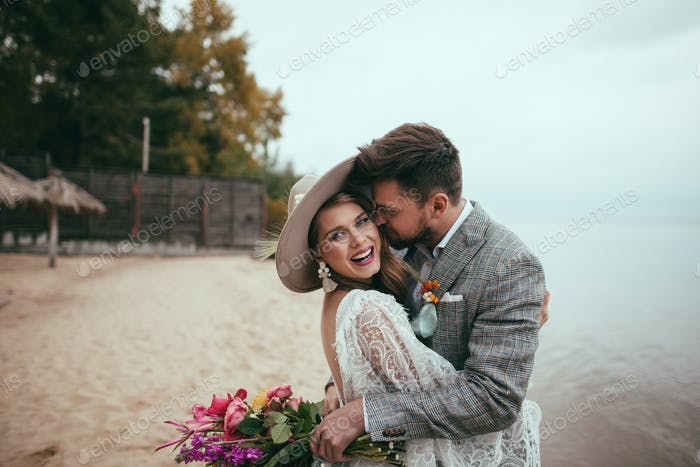 Happy Bride and Groom in Boho Style Embracing on Beach