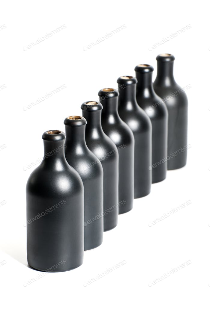 A set of several empty black bottles on a white background close