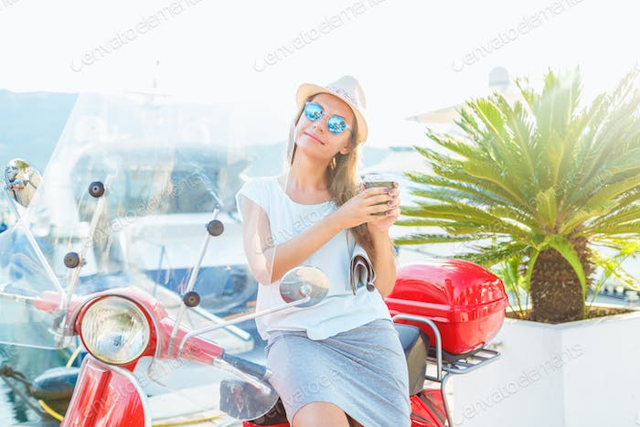 Happy young woman drinking takeaway coffee near her red moped in