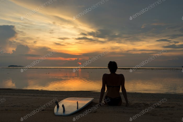 surfer girl, model, woman looking at ocean or sea beach sunset.