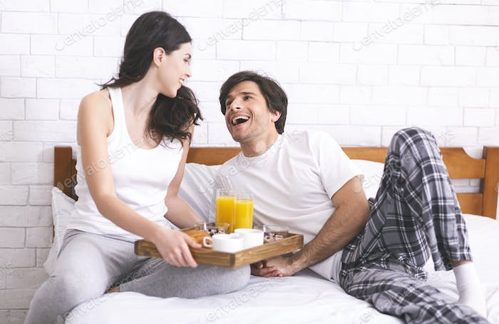 Loving wife bringing tray with food for her husband