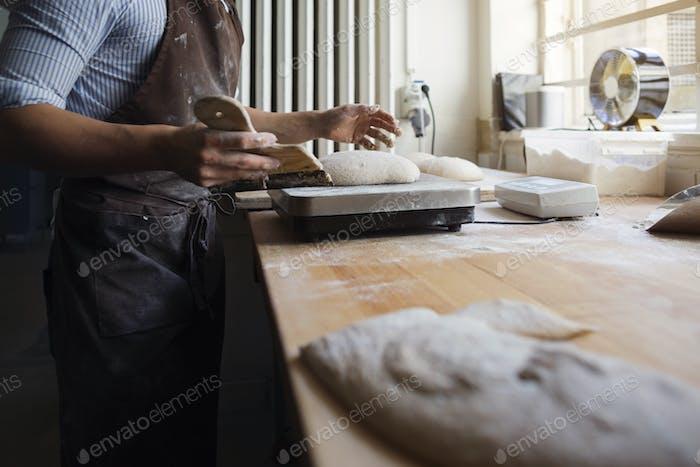 Baker using kitchen scale in kitchen