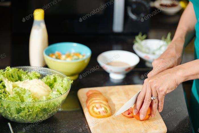 Housewife cutting fresh tomatoes