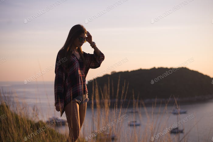 Hipster stylish woman traveler looking on a sea or ocean at the sunset