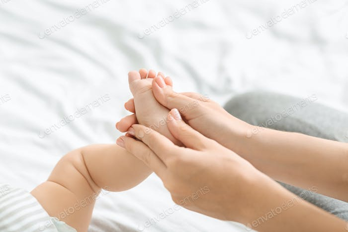 Mother massaging little baby's foot, making strengthening gymnastic