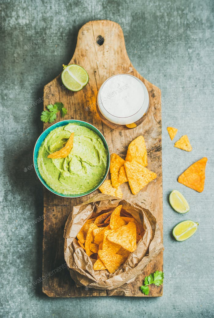 Mexican corn chips, fresh guacamole sauce and beer, wooden board