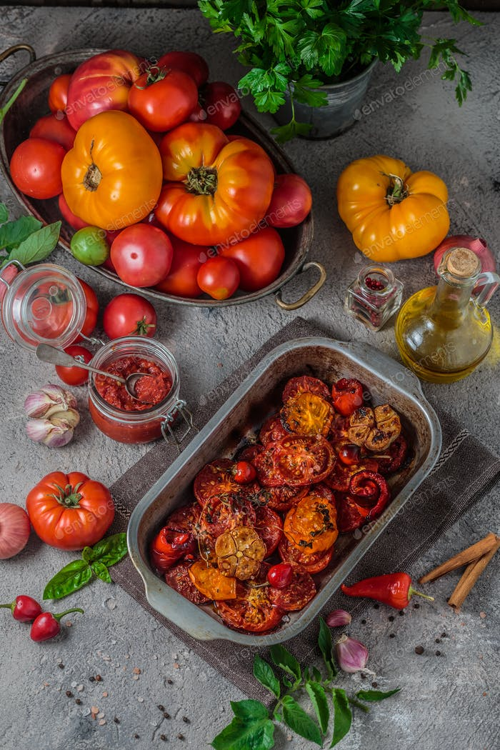 Baked tomatoes in a metal tray with ripe tomatoes on background, top view