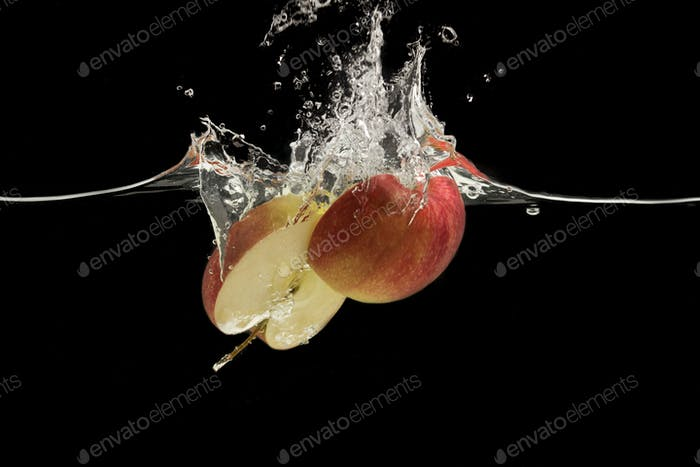 Red apple cut in half splashing into water on black background