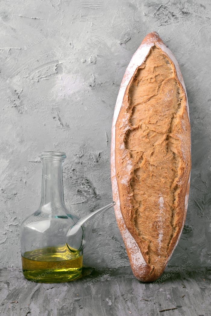 loaves of rustic bread and oil resting on gray marble background