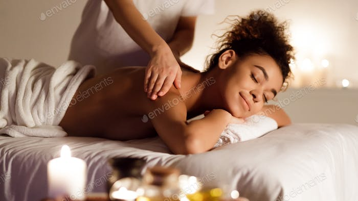 Millennial afro lady enjoying back massage in spa