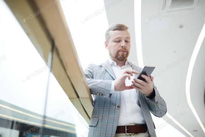 Serious businessman checking messenger