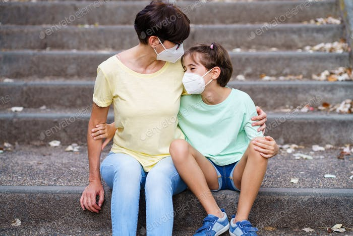 Placeit - Middle-aged mother and daughter sit on the street wearing masks