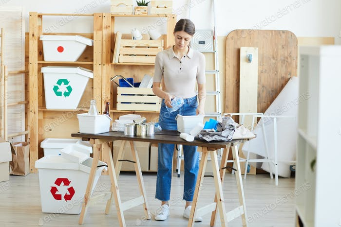 Woman recycling waste in warehouse