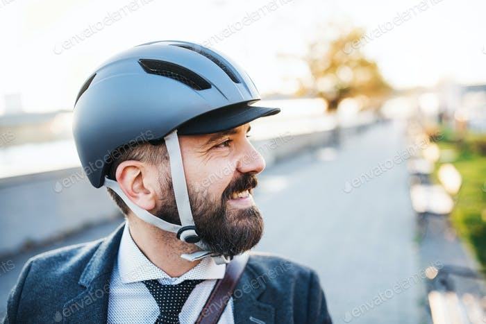 Businessman commuter with bicycle helmet traveling home from work in city.