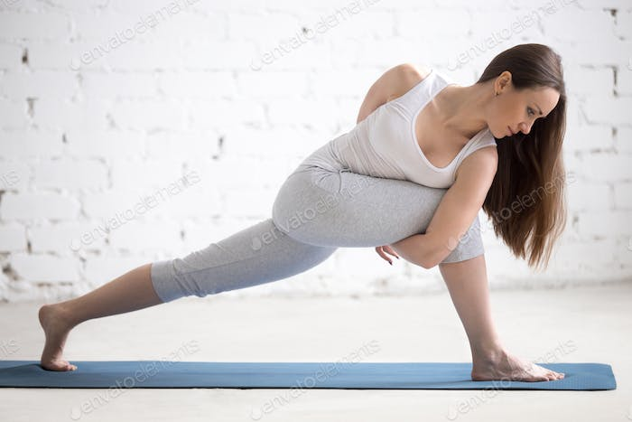 Profile portrait of young woman doing Revolved Side Angle Pose